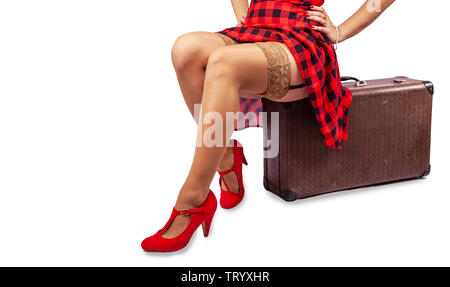 woman in red dress and nylon stockings sitting on a suitcase isolated on  white. legs closeup - Stock Image