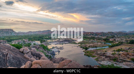 A gorgeous view over a rocky landscape with a river at sunset - Stock Image