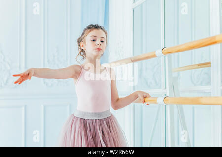 Young classical ballet dancer girl in dance class. Beautiful graceful ballerina practice ballet positions in pink tutu skirt near large mirror in whit - Stock Image
