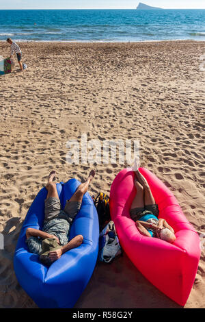 Male and female tourists sitting on blue and red inflatable lips beach furniture sunbathing on an air lounger on the beach - Stock Image