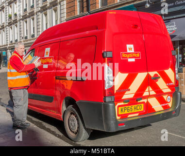 Royal Mail adult male / man delivery driver and van, delivering letters and packages in the centre of London on - Stock Image