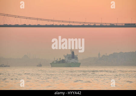 A cargo ship sails under the first Bosphorus Bridget towards the historic part of Istanbul and the Sea of Marmara. - Stock Image