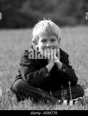 young boy sitting in grass - Stock Image