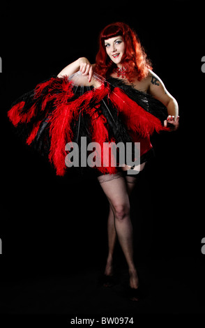 Burlesque Performer Dancing with Red and Black Fans - Stock Image