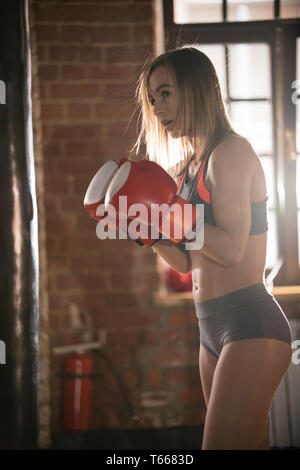 An athletic woman in boxers gloves on training in the gym - Stock Image
