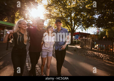 A group of best friends hanging out together and walking through a park. Friends all having a good time and smiling. - Stock Image