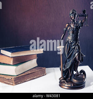 Themis figurine stands on a white wooden table next to a stack of old books. Scales Law Lawyer Business Concept. - Image - Stock Image
