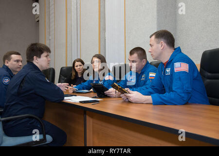 International Space Station Expedition 59 prime crew members Christina Koch of NASA (second from the left), Alexey Ovchinin of Roscosmos (second from the right) and Nick Hague of NASA (right) review flight plan activities at the Baikonur Cosmodrome March 9, 2019 in Baikonur, Kazakhstan. Expedition 59 crew will launch March 14th onboard the Soyuz MS-12 spacecraft for a six-and-a-half month mission on the International Space Station. - Stock Image