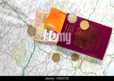 A British passport, Euro coins and notes on a road map of Spain, illustrating the concept of travel, journey, or - Stock Image