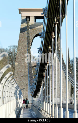 An Asian couple, man and woman, holding hands. taking a brisk winter stroll across the Clifton Suspension bridge, - Stock Image