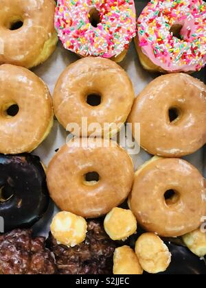 A box of colorful donuts. - Stock Image