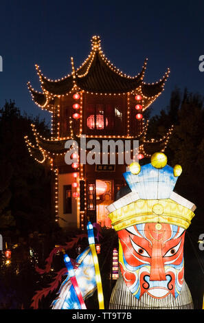 The Dream Lake and the Magic of Lanterns exhibit with the Tower of Condensing Clouds pavilion at dusk in the Chinese Garden, Montreal Botanical Garden - Stock Image