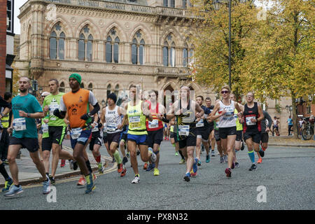 Chester, UK. Runners taking part in the 2018 Chester Marathon pass in front of the Town Hall - Stock Image