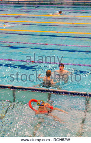 Poznan, Poland - January 26, 2019: Children and a adult during swimming lessons in a pool in the Termy Maltanskie. - Stock Image