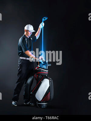 Male golfer removing glowing golf club from bag - Stock Image