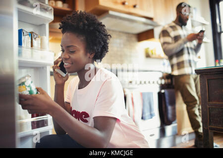Woman talking on smart phone, reading label on jar in refrigerator in kitchen - Stock Image
