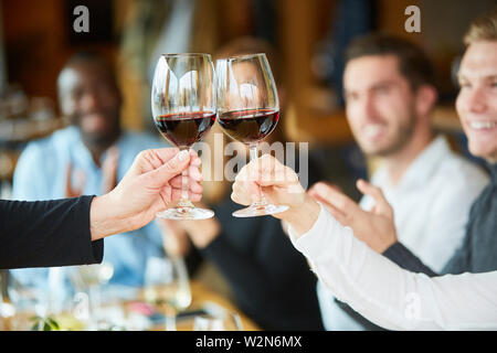 Friends celebrate a party together in the restaurant and toast with red wine - Stock Image