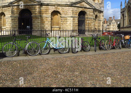 Bicycles chained to railings by the Radcliffe Camera, Oxford - Stock Image