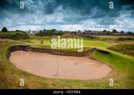 Prestwick Golf Club Green and huge bunker  under dark clouds threatening skies golf in Scotland - Stock Image
