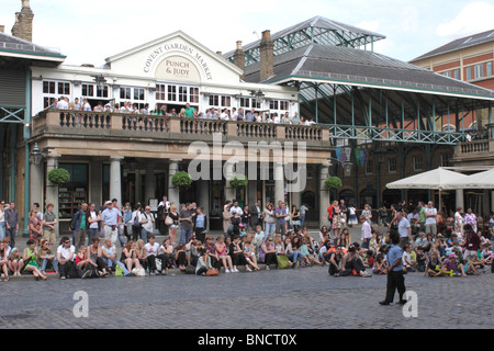 Street entertainer facing crowd of spectators at Covent Garden London summer 2010 - Stock Image