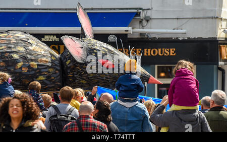 Brighton UK 4th May 2019 - A tableau depicting the Pied Piper of Hamelin followed by a giant rat amongst the thousands of schoolchildren , teachers and parents taking part in the annual Brighton Festival Children's Parade through the city which has the theme 'Folk Tales from Around the World' . Organised by the Same Sky arts group the parade traditionally kicks off the 3 week arts festival with this years guest director being the singer songwriter Rokia Traore . Credit : Simon Dack / Alamy Live News - Stock Image
