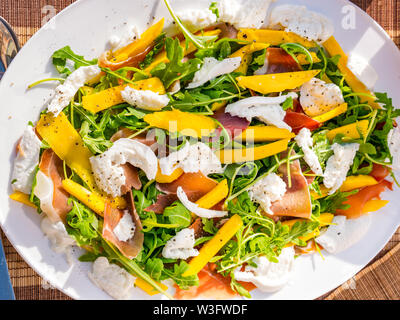 Summer food: salad meal served outdoors with mango slices, rocket and parma ham on a white plate - Stock Image