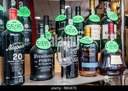 Bottles of aged Port wine for sale in a wine shop window, Lisbon, Portugal - Stock Image