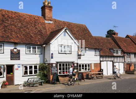 Cyclists resting by The Chequers Inn 14thc village pub in a white clapboard Kentish building in Smarden Kent England UK Britain - Stock Image