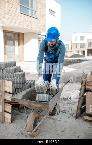 Builder loading paving tiles into the pushcart standing on the construction site - Stock Image