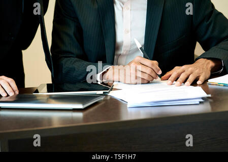 Businessman signing a document in office - Stock Image