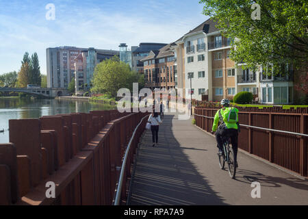 Commuters head for work along the side of the Thames in reading, Berkshire. - Stock Image