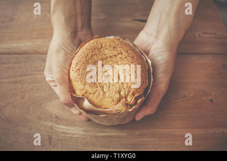 Female hands holding egg cupcake on wooden table, homemade - Stock Image