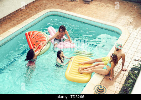 Happy friends having fun in swimming pool during summer vacation - Young people relaxing and floating on air lilos in the pool resort - Stock Image