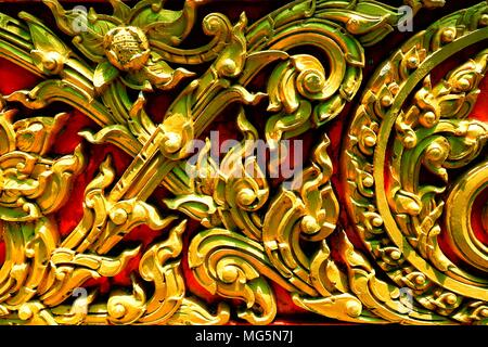 Closed-up Vintage Golden Thai Sculpture on Stone Wall. - Stock Image
