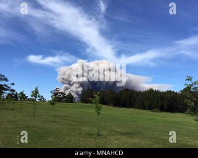 Kilauea Volcano, Hawaii. 15th may 2018. A grey ash plume rises from the Halemaumau crater in the Kilauea volcano seen from the Volcano Golf Course May 15, 2018 in Hawaii. The recent eruption continues destroying homes, forcing evacuations and spewing lava and poison gas on the Big Island of Hawaii. Credit: Planetpix/Alamy Live News - Stock Image