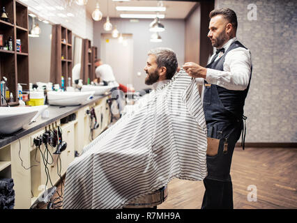 Handsome hipster man client visiting haidresser and hairstylist in barber shop. - Stock Image