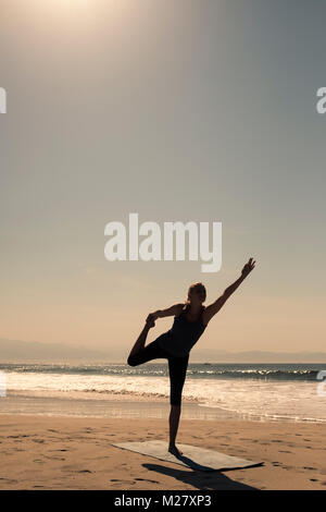 A young woman is exercising a stand up yoga pose at a beach - Stock Image