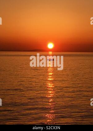 Small sailing through a sunset - Stock Image