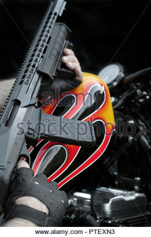 Modern Weapon Held Over a Custom Flame Painted Bikie Style Motorcycle - portrait/vertical aspect - Stock Image