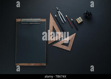 Black on black flat lay with a clipboard, pencils, and rulers. Drawing blueprints header with copy space. - Stock Image