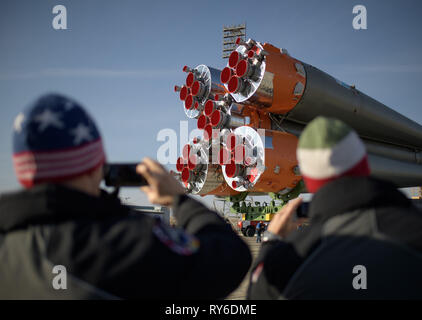 Baikonur, Kazakhstan. 12th Mar, 2019. Expedition 59 backup crew members Drew Morgan of NASA, left, and Luca Parmitano of the European Space Agency, right, watch the Russian Soyuz MS-12 rocket as it is transported by train to the launch pad at the Baikonur Cosmodrome March 12, 2019 in Baikonur, Kazakhstan. The Expedition 59 crew: Nick Hague and Christina Koch of NASA and Alexey Ovchinin of Roscosmos will launch March 14th for a six-and-a-half month mission on the International Space Station. Credit: Planetpix/Alamy Live News - Stock Image