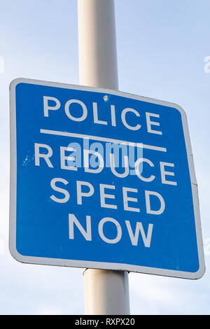 Blue and white pole mounted police reduce speed now sign on the seafront St Annes on Sea Fylde Coast February 2019 - Stock Image