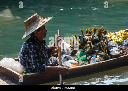 Damnoen Saduak - 4th March 2014: A woman vendor paddles her boat along the canal. The town is famous for its floating market. - Stock Image