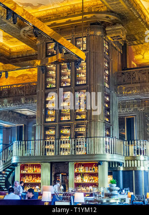 Tall cabinet or gin tower with glass and carved wooden columns the  centerpiece of the Atlas bar in the lobby of Parkview Square Singapore. - Stock Image