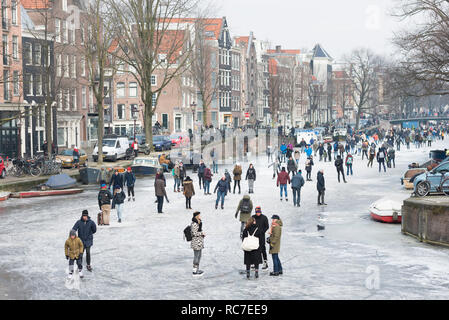 Ice skating people on frozen canal Prinsengracht, Amsterdam, The Netherlands. - Stock Image