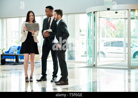 Business people standing and discussing in the hotel lobby - Stock Image