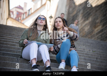 Two young women sitting on stairs holding a map and looking straight. Mid shot - Stock Image