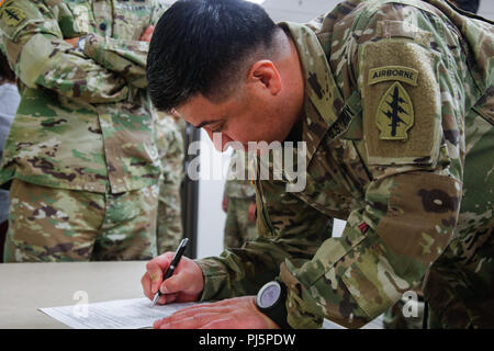 JOINT BASE LEWIS-MCCHORD, Washington – CW2 Gustavo Salvador, a property book officer with the 1st Special Forces Group (Airborne), signs his oath of a commission, August 24, during his promotion ceremony. Salvador immigrated to the United States from Ecuador to enlist in the U.S. Army, and through his dedication to the Army's mission and his demonstrated proficiency, he has both earned our nation's trust, and his commission as an officer. (U.S. Army photo by Sgt. Ian Ives, 1st Special Forces Group (Airborne) /Released). - Stock Image