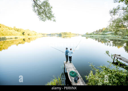 Landscape view on the beautiful lake with two male friends fishing together standing on the wooden pier during the morning light - Stock Image