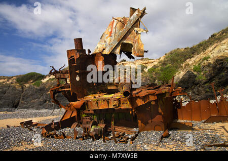 Profile of a wrecked pusher boat withered to pieces on the beach. The bridge is floating over tge hull and above - Stock Image